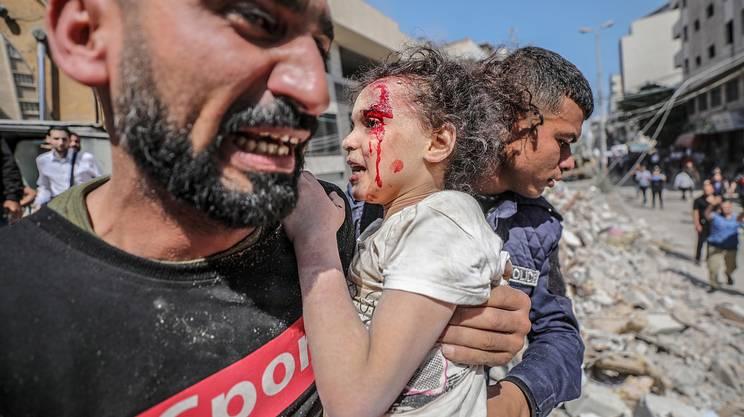 Un uomo palestinese porta il figlio ferito a Gaza City