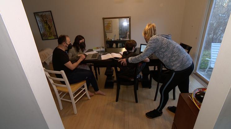 In tuta, in sala da pranzo, genitori che aiutano i figli durante le lezioni a distanza