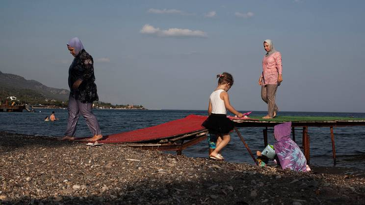 Alcune donne turche con il costume da bagno coperto (cosiddetto burqini) stanno tornando alla spiaggia dopo una nuotata. Assos / Ayvacık / Çanakkale, Turchia occidentale, il 12 agosto 2016