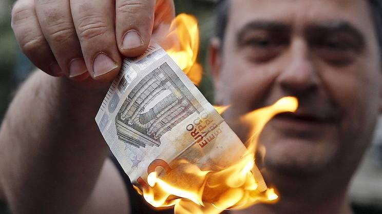 Davanti al Parlamento ad Atene, un manifestante antiausterità brucia cinque euro