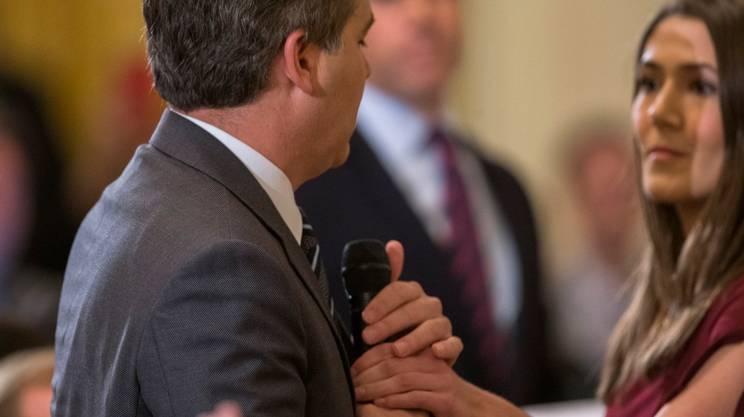 La dipendente della Casa Bianca mentre tenta di togliere il microfono al giornalista, ci riuscirà