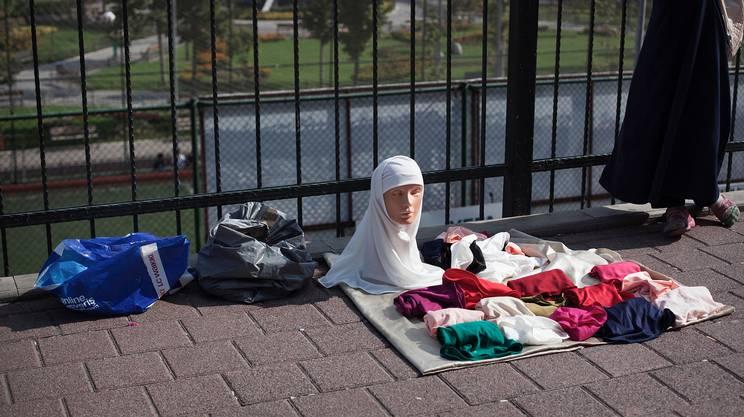 Ragazza senza testa. Nel quartiere conservatore di Fatih una giovane vende per strada i tradizionali veli islamici. Istanbul, il 31 Agosto 2016.