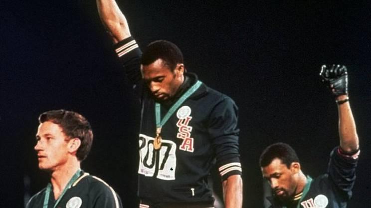 """Tommie Smith, al centro, e John Carlos a destra. L'australiano Peter Norman, a sinistra, fu solidale alla protesta, indossando sul podio uno stemma del """"Progetto Olimpico per i Diritti Umani"""", in solidarietà con gli atleti afro-americani"""