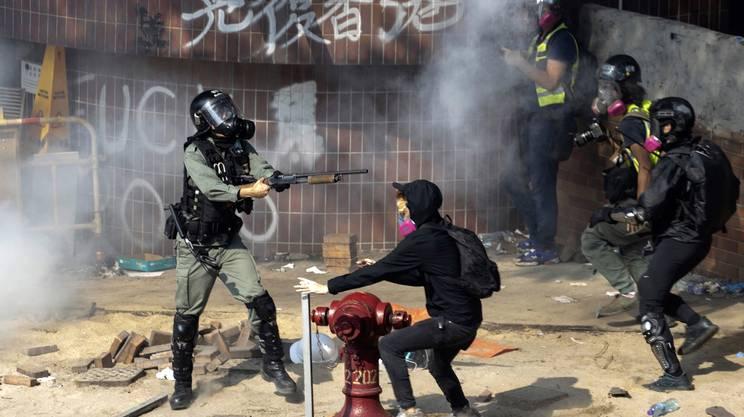 Un agente della polizia di Hong Kong punta il fucile ad altezza uomo