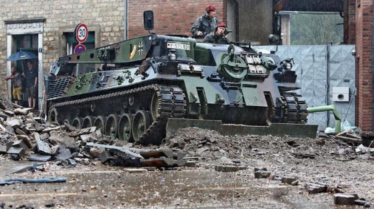 Un carro armato cerca di liberare le strade di Aquisgrana dai detriti delle esondazioni