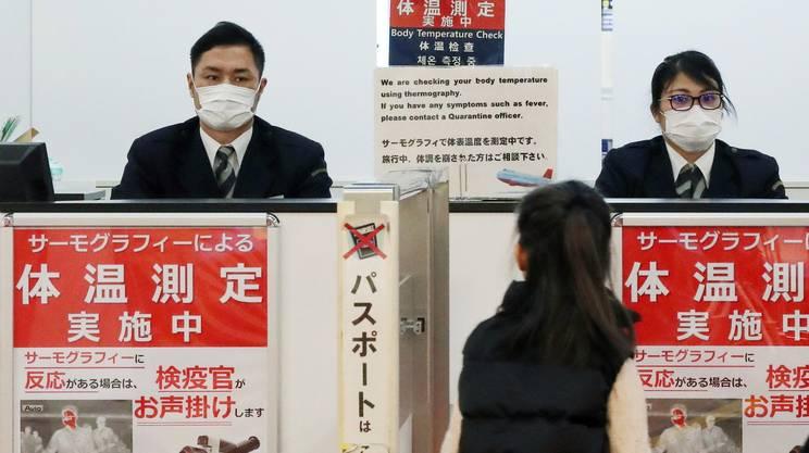 Una passeggera passa i controlli di quarantena all'aeroporto di Narita, in Giappone