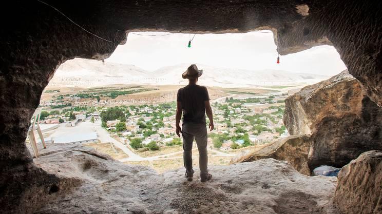 Un ragazzo osserva Hasankeyf, sulle rive del fiume Tigri, da una delle antiche grotte che un tempo furono abitazioni