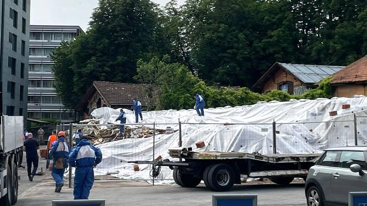 Lavoratori all'opera in tenuta di sicurezza per coprire le macerie dell'Ex Macello