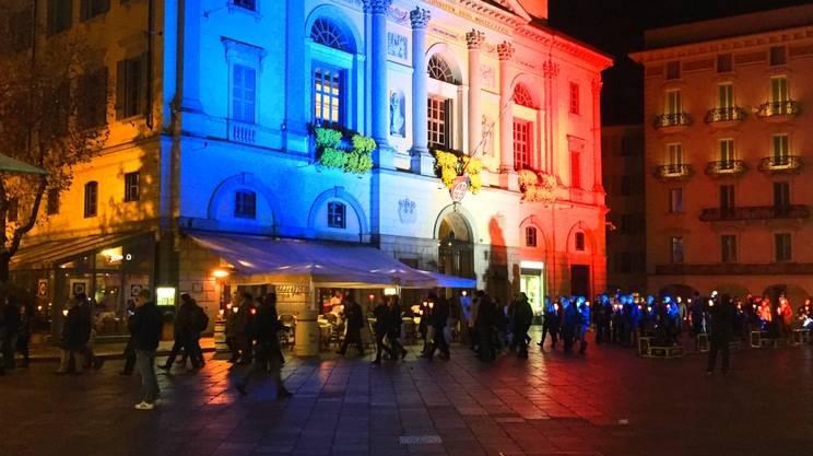 Un momento della fiaccolata con la sede del Municipio in versione tricolore