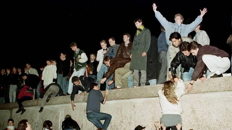 I cittadini della Germania dell'Est scalano il muro di Berlino alla Porta di Brandeburgo, il 10 novembre 1989