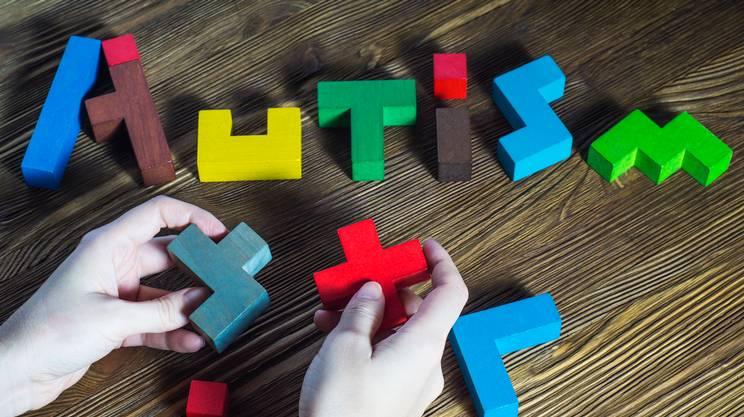 Parola autismo costruito in legno Puzzle su uno sfondo in legno