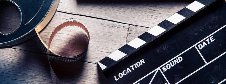 Bobina di Film e Film clapper su sfondo in legno, Film, Industria cinematografica, Ciac cinematografico, Regista, Industria