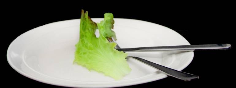 Concetto dieting, mangiare vegetariano o Disturbo alimentare. Lattuga sul piatto