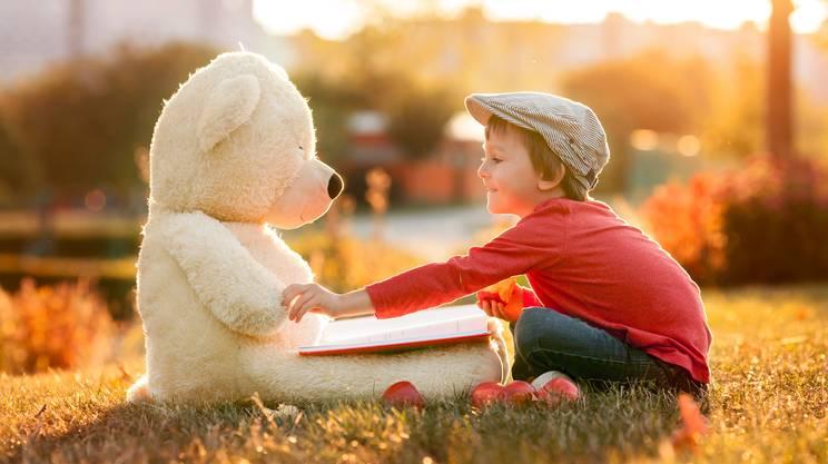 piccolo ragazzo con orsacchiotto amico nel parco, leggere libro