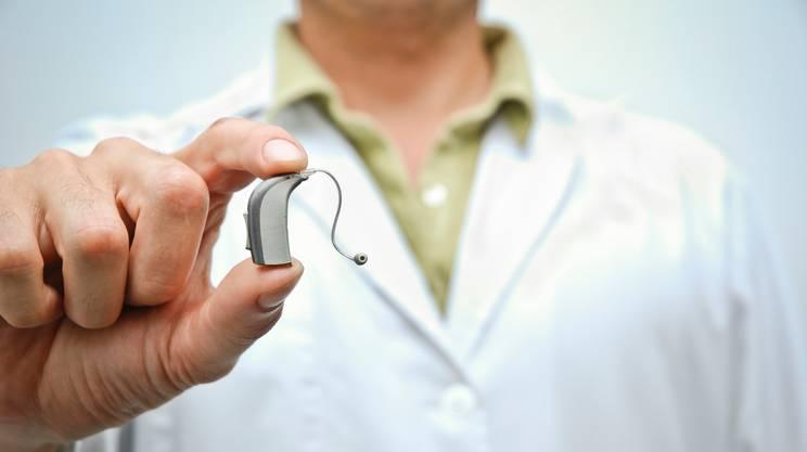 Medico mostrando Apparecchio acustico
