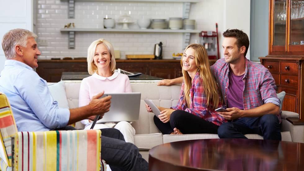 Genitori con Prole adulta utilizzando dispositivi digitali in casa, non lasciare il nido di casa