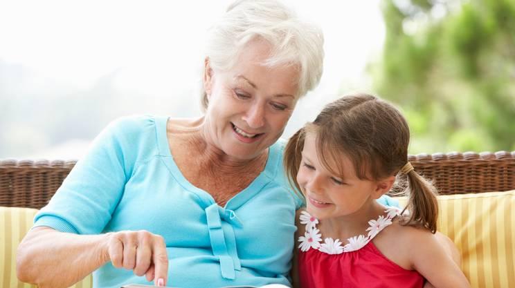 Nonna e nipote leggere libro sul giardino sedile