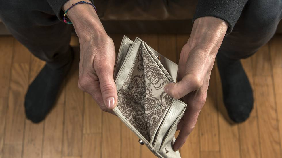 Poverta', in Ticino, mani di donna che aprono il suo borsellino vuoto